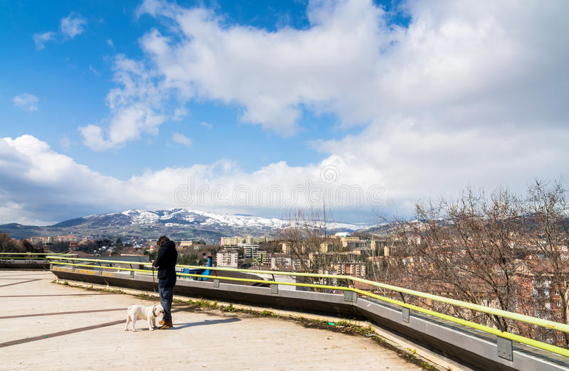 Panoramic day view of Potenza, Italy. POTENZA, ITALY - MARCH 13, 2015: unidentified person with dog, panoramic view of city and mountains in Potenza, Italy royalty free stock image