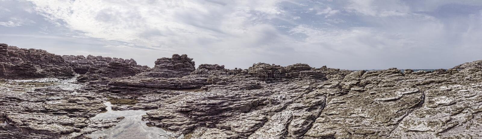 Panoramic 180 degree view of wilderness pristine with ancient geological rocks layers formation carved by wind.  stock photos