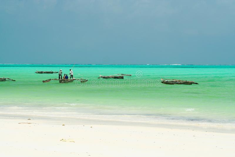 Panoramic endless view over white sand on turquoise green water with wooden traditional dau sailing boats - Paje beach, Zanzibar royalty free stock photo