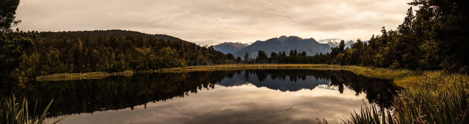 Panoramic famous twilight reflected view of beautifully romantic Aoraki/Mt Cook and Mount Tasman on water of Lake Matheson royalty free stock images