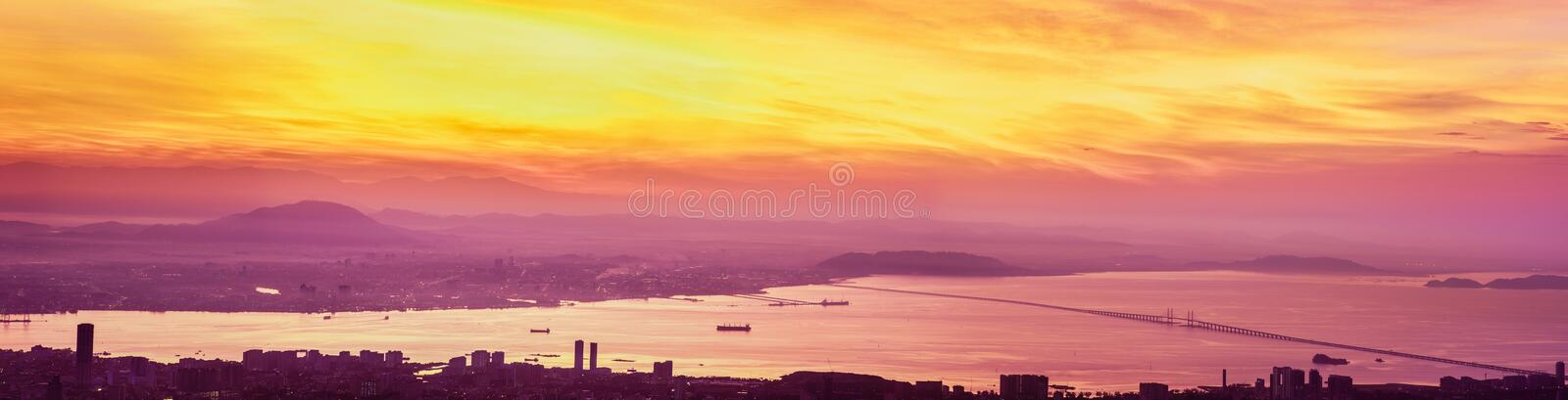 Panoramic Flame of Sunrise Over Pulau Penang. A panoramic view of a spectacular sunrise from Penang Hill overlooking George Town, Seberang Perai and Penang stock images