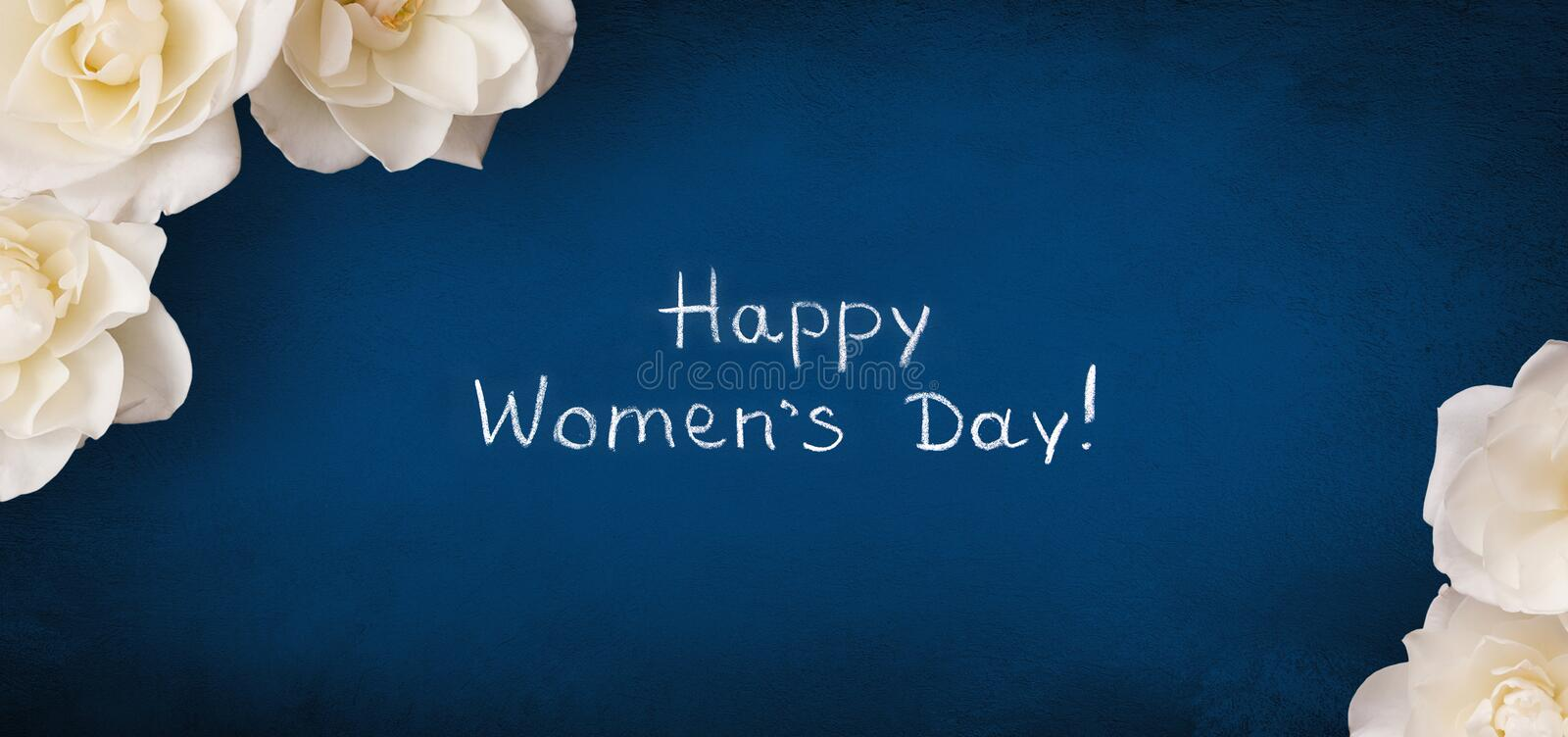 Panoramic greeting card 8 March Happy Women`s Day. Text Happy Women`s Day written by chalk on blue background decorated with white rose flowers. Top view. Flat stock photography