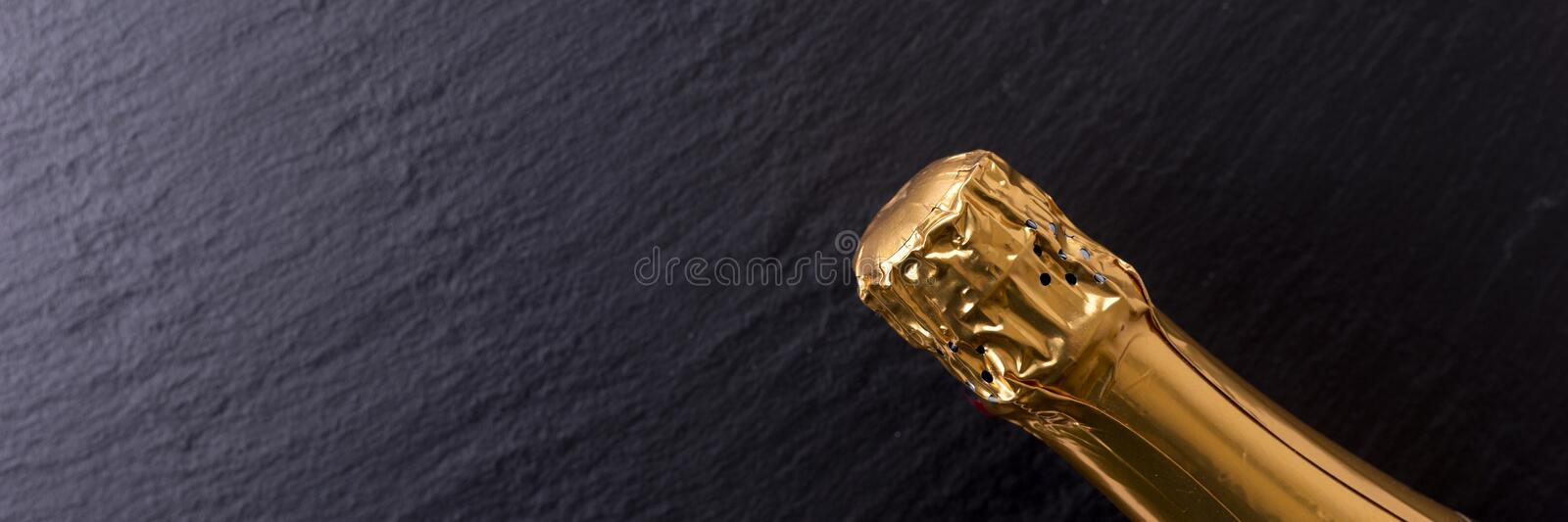 Panoramic image. Champagne bottle on black slate plate royalty free stock photography