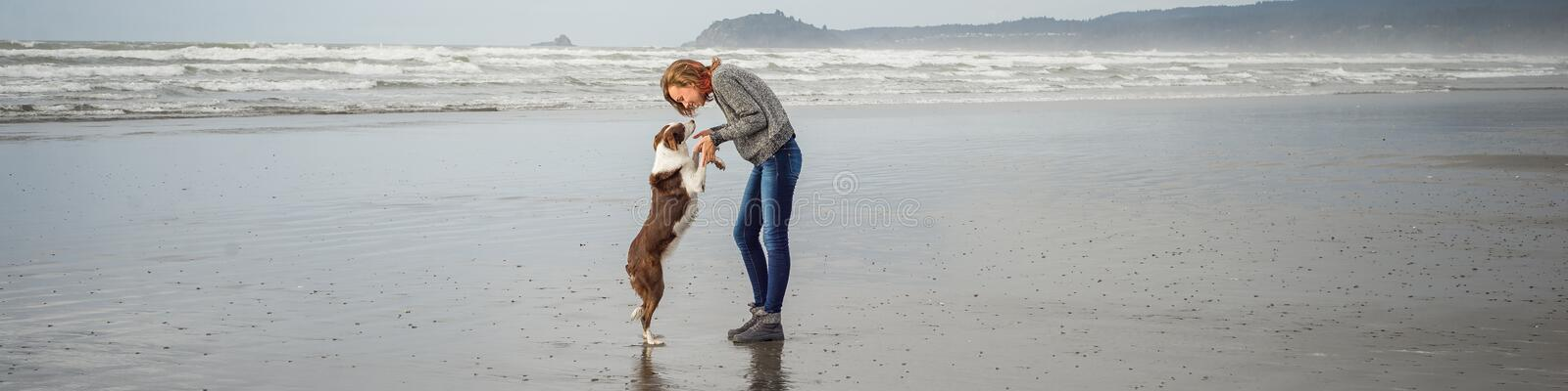 Panorama of a young woman and her Border Collie dog together on a Northern California beachog standing on it`s back stock photos