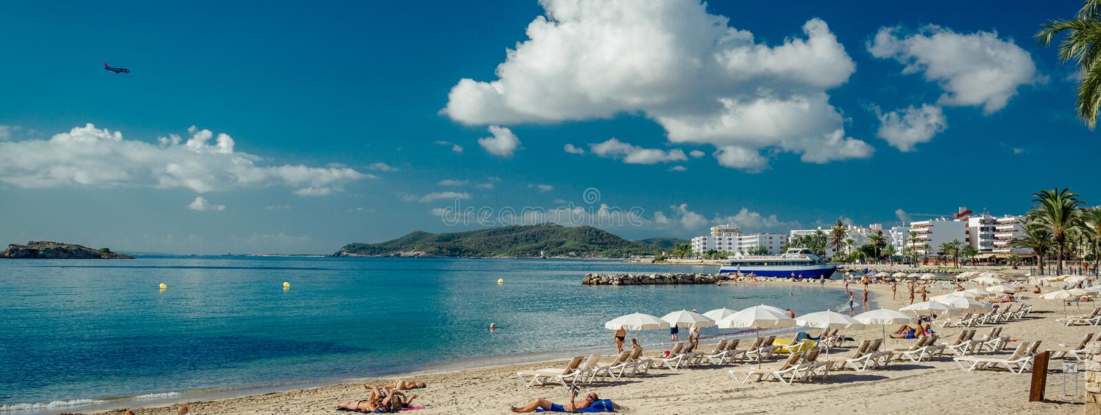 Panoramic image people sunbathing on Ibiza coast, Spain. Panoramic image people sunbathing on Ibiza coast, sandy beach. Spanish famous place which is filled with stock photography
