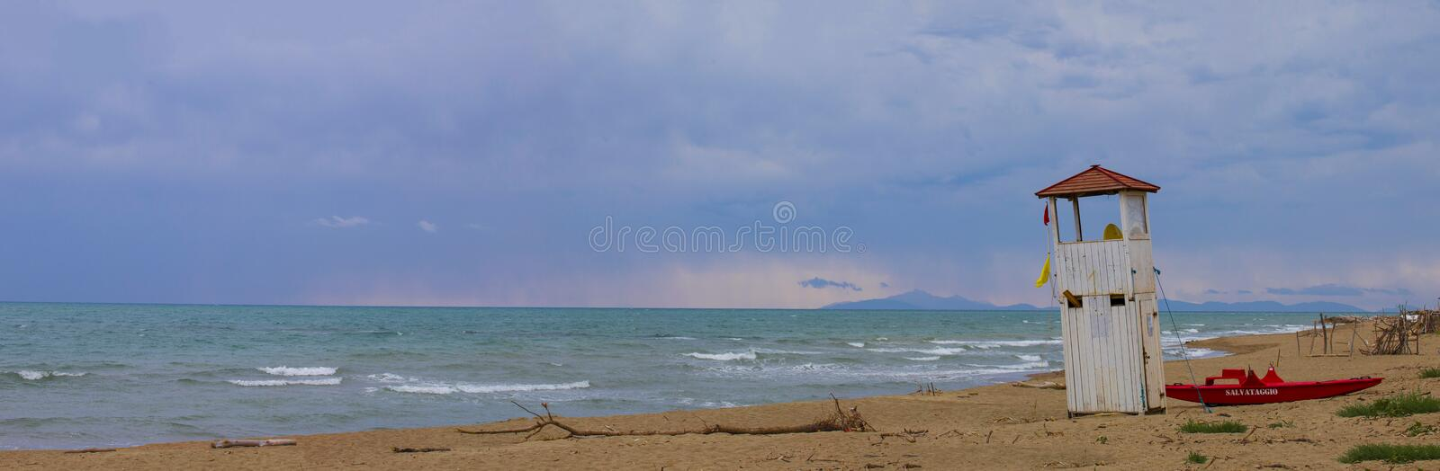 panoramic image of a seascape with desolate sand beach and a lifeguard tower and rowing boat stock image