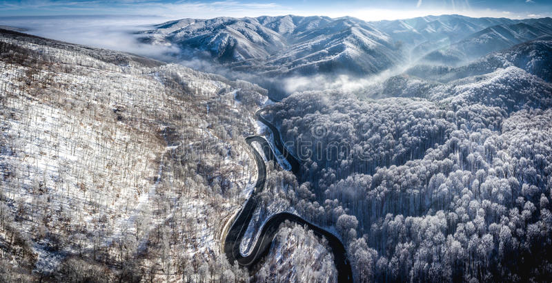 Panoramic image of a winding road from a high mountain pass in T. Ransylvania in the winter with sno covered mountains visible in the back royalty free stock photos