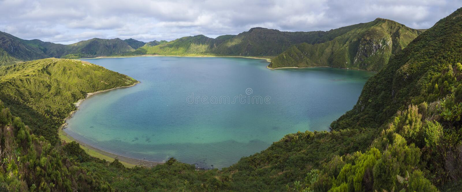 Panoramic landscape with beautiful blue crater lake Lagoa do Fogo from top of the hill on hiking trail. Lake of Fire is. The highest lake of Sao Miguel island royalty free stock photo