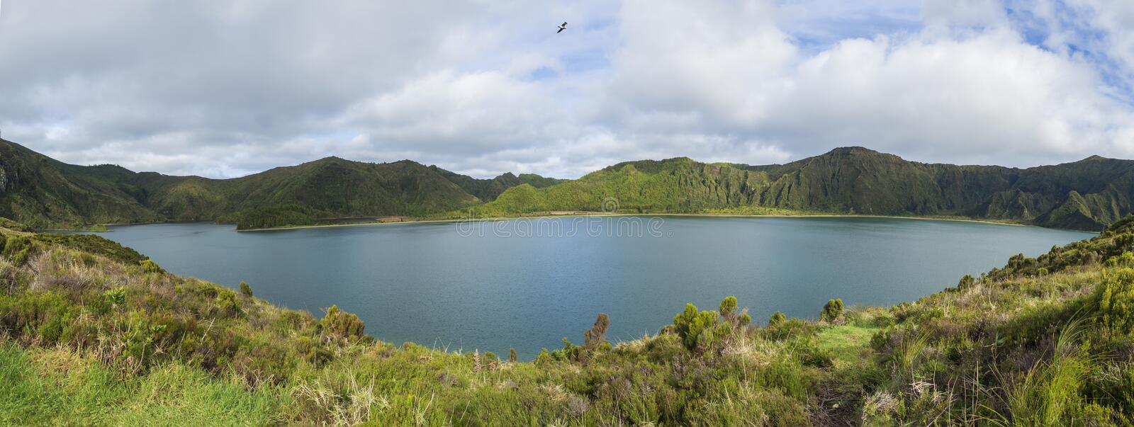 Panoramic landscape with beautiful blue crater lake Lagoa do Fogo from top of the hill on hiking trail. Lake of Fire is stock photos