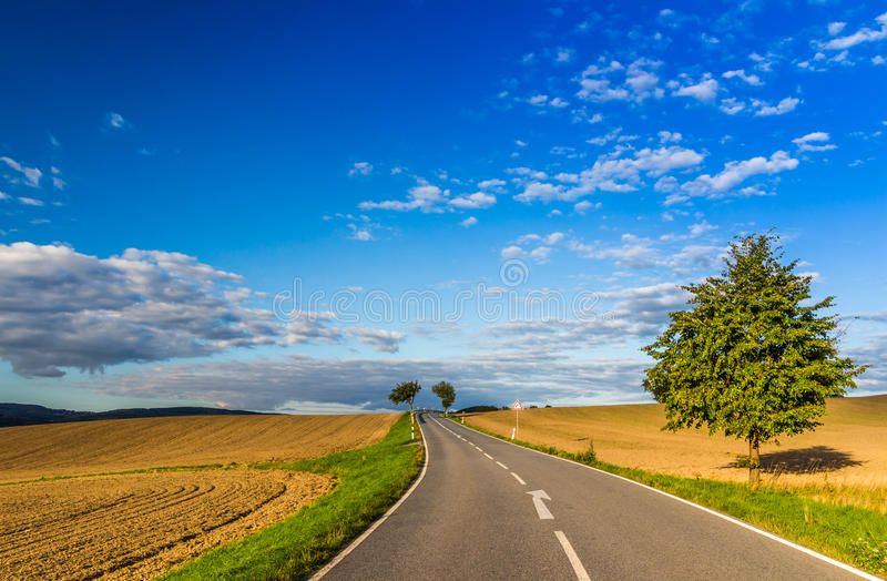 Panoramic landscape of colorful yellow-green hills with ground road, blue sky and clouds stock images