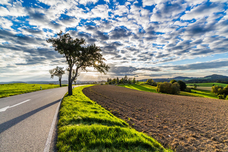 Panoramic landscape of colorful yellow-green hills with ground road, blue sky and clouds stock photography