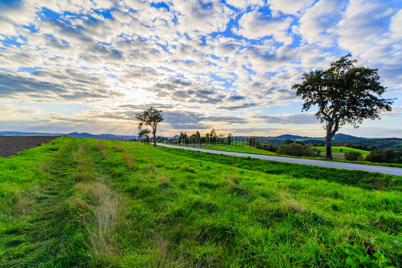 Panoramic landscape of colorful yellow-green hills with ground road, blue sky and clouds stock photos