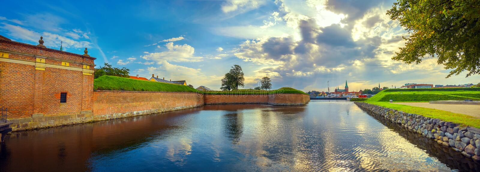 Fortress walls and moat with water in Kronborg castle at sunset. Helsingor, Denmark. Panoramic landscape with fortress walls, water moat of Kronborg castle and royalty free stock photo