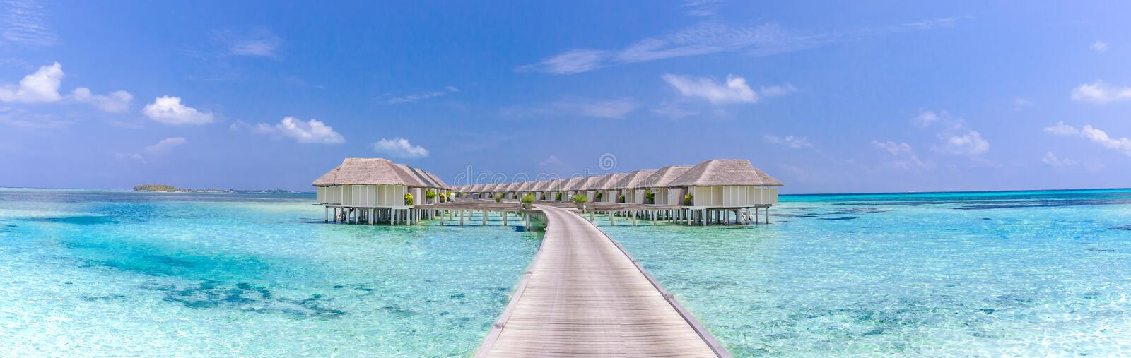 Panoramic view of a Maldives tropical island, luxury water villas over calm blue sea royalty free stock image
