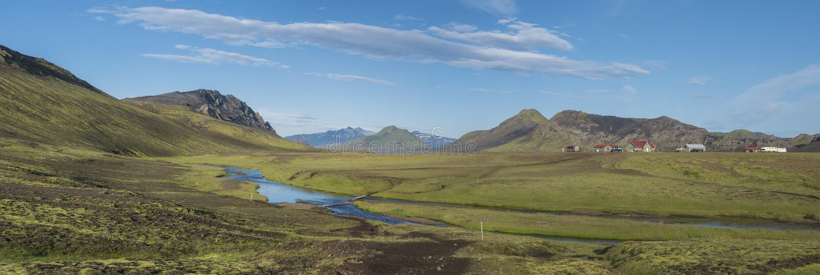 Panoramic landscape with mountain huts at camping site on blue Alftavatn lake with river, green hills and glacier in stock photo