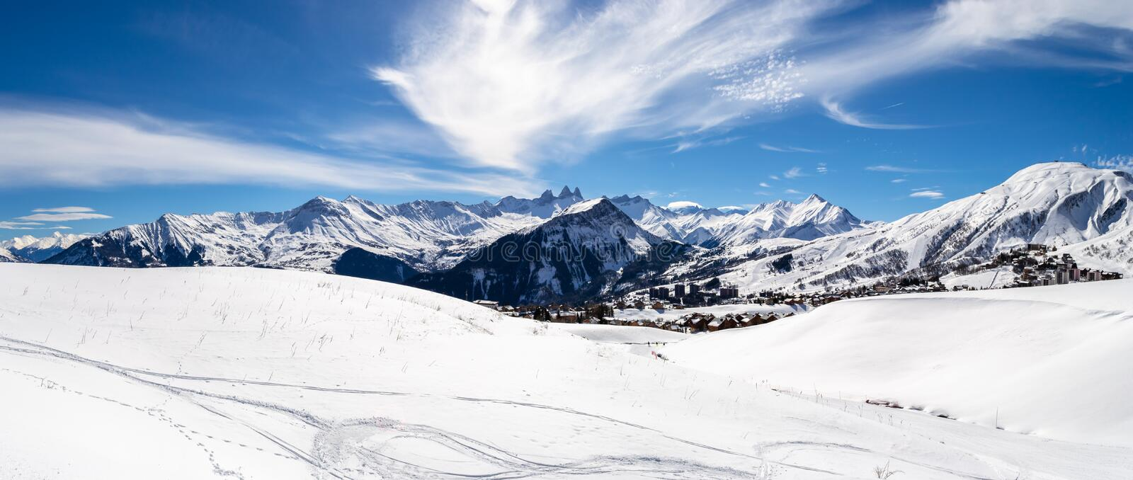 Panoramic landscape with mountain peaks in the French Alps, above La Toussuire village, on a sunny Winter day, in Les Sybelles. Ski area stock photo
