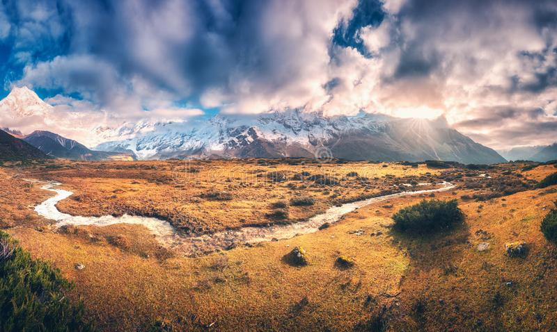 Mountains with snow covered peaks in purple clouds and river. Panoramic landscape with mountains with snow covered peaks in purple clouds, sun, small river royalty free stock images