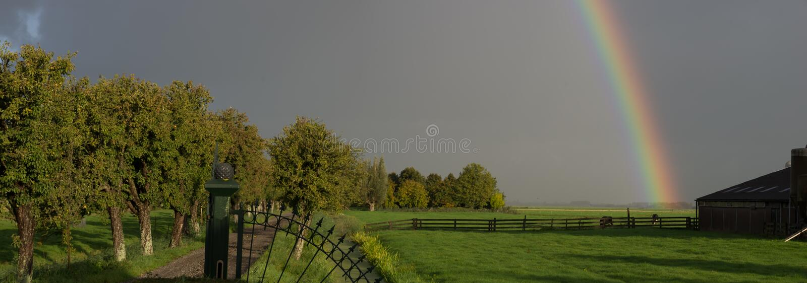 Panoramic landscape with rainbow at farmland in Woerden, Netherlands. Farmland and entrance gate with morning rainbow sky in Woerden, Netherlands stock photography