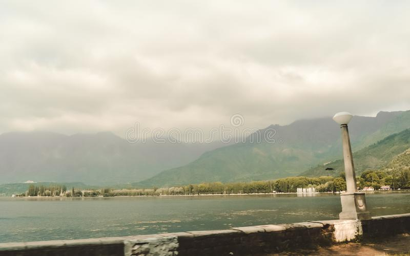 Panoramic Landscape scenery pristine beauty of world famous Dal Lake, Srinagar, Jammu and Kashmir, India. The Great Himalayas. Range cloudscape at a distance royalty free stock image