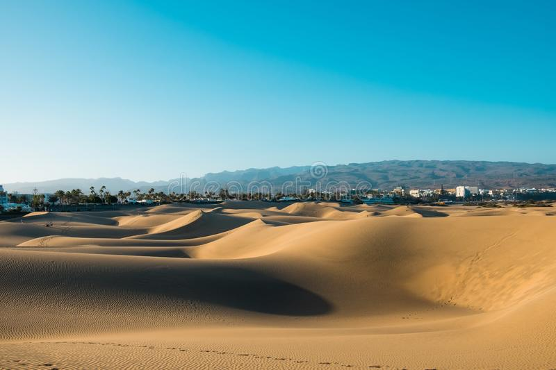 Panoramic landscape view of maspalomas sand desert dunes with the city and mountains in background on a sunny summer day royalty free stock photos