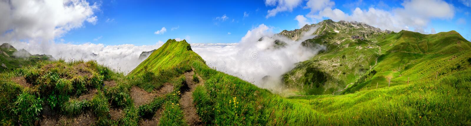 Panoramic majestic alpine view. Extra wide Panoramic majestic view on the Bavarian Alps and the Nebelhorn mountain with blue sky and white clouds stock photos