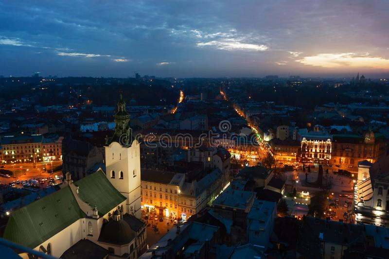 Panoramic night cityscape view on roofs,lights center and domes of Lviv city, Ukraine with a sun flare stock photos