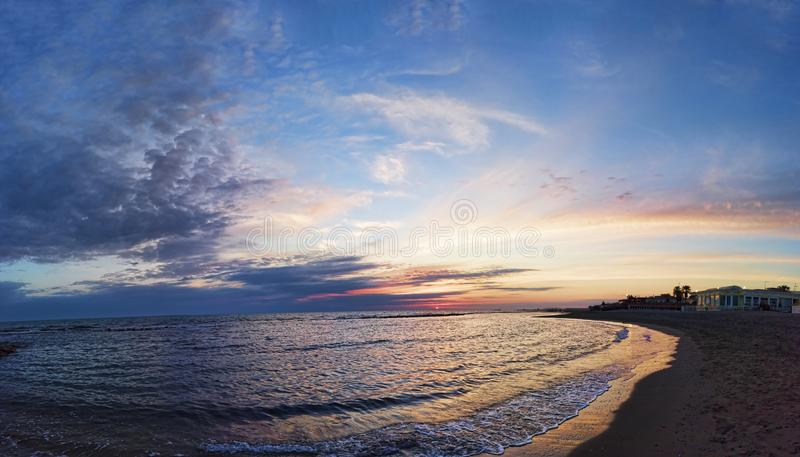 Panoramic pastel-colored sunset on the coast of Rome, with awesome sky , the calm sea and a relaxing atmosphere. Panoramic blue sunset on Roman coast at Ostia royalty free stock photography
