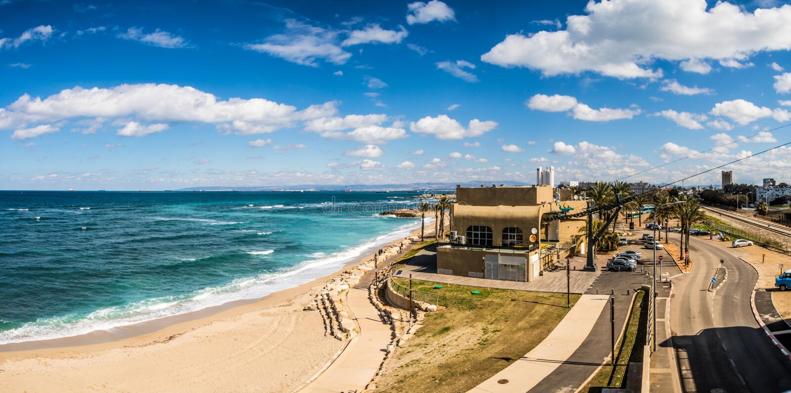 A panoramic photo of a beach in Haifa, Israel. With clouds in the sky stock photo