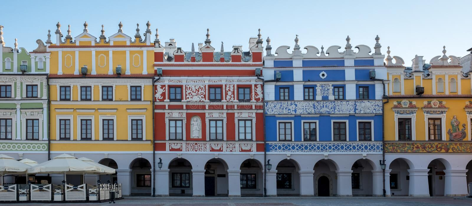 Panoramic photo of brightly coloured renaissance buildings in the historic Great Market Square in Zamosc in southeast Poland. royalty free stock image