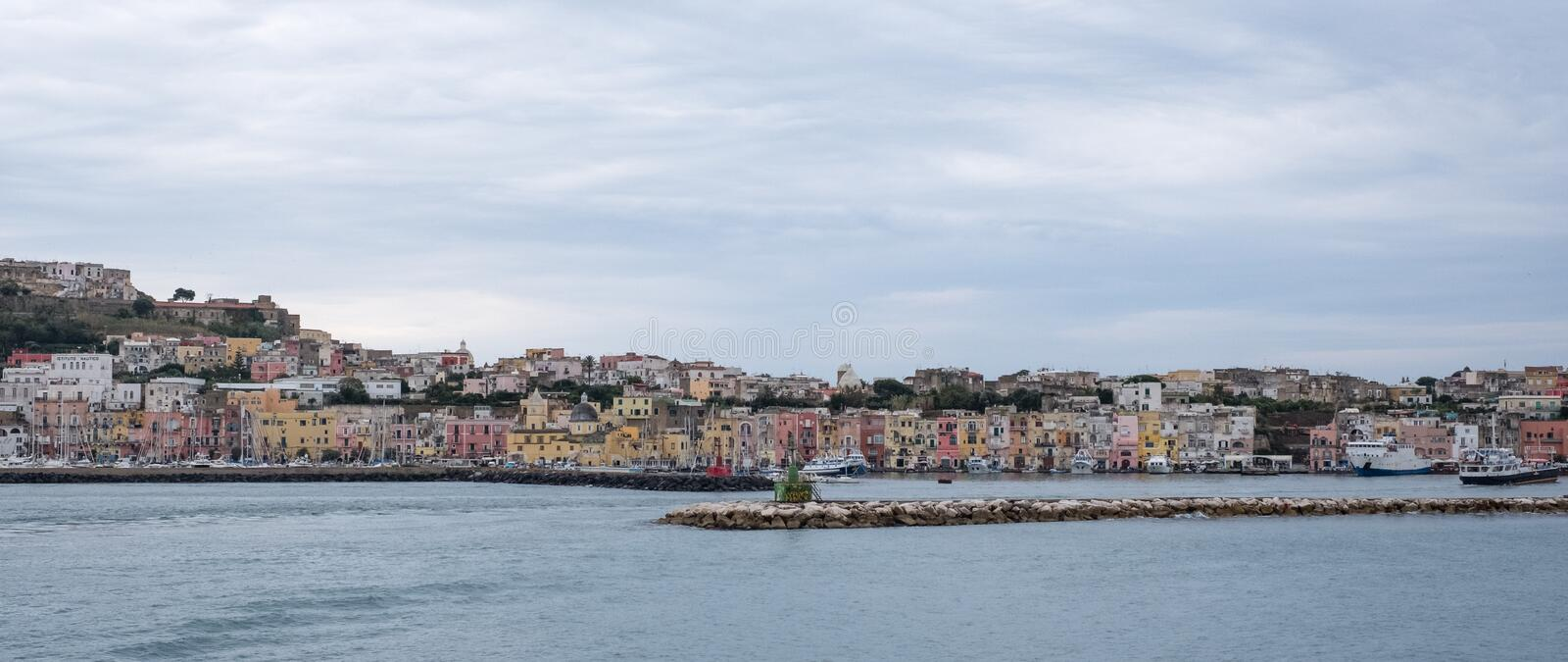 Panoramic photo of the harbour front with pastel coloured houses on the island of Procida Italy, photographed from the water. stock photography