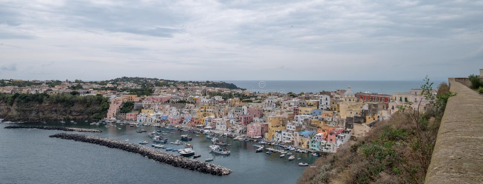 Panoramic photo of Marina Corricella, Italy, fishing village on the island of Procida with pastel coloured houses stock photography