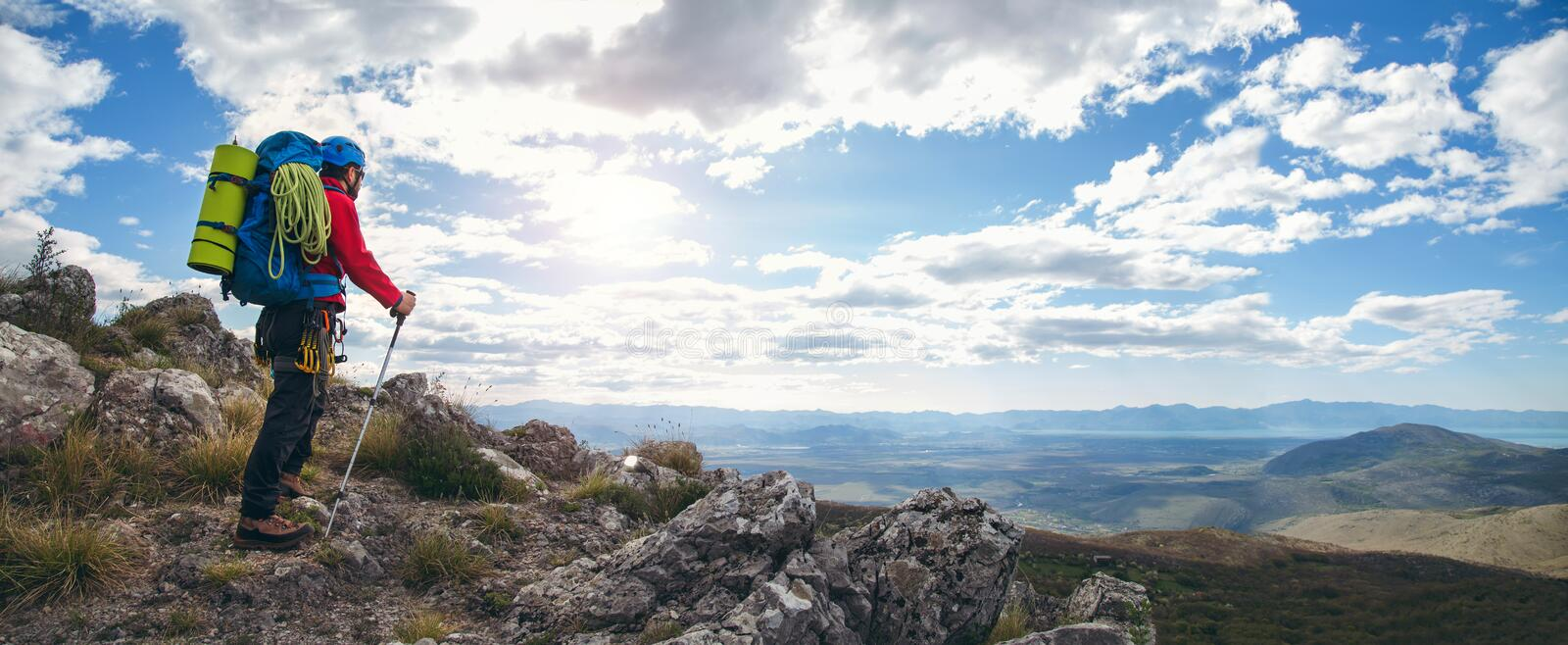 Panoramic photo of mountaineers standing with backpack. On top of a mountain and enjoying the view stock photo