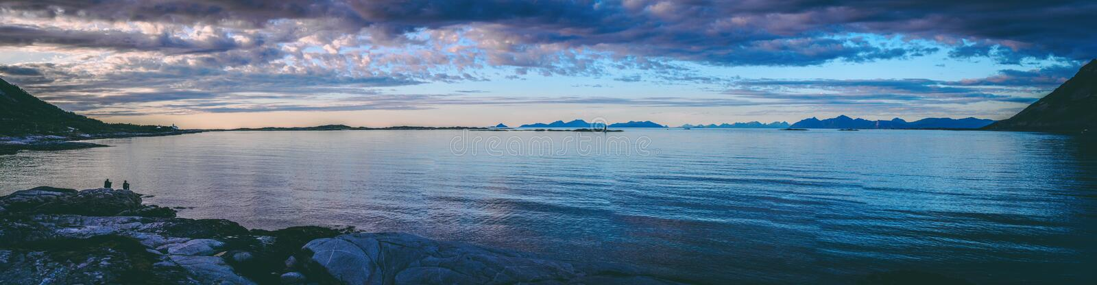 Panoramic photo of people sitting on a rocky seashore at sunset in Norway. In the evening stock photography