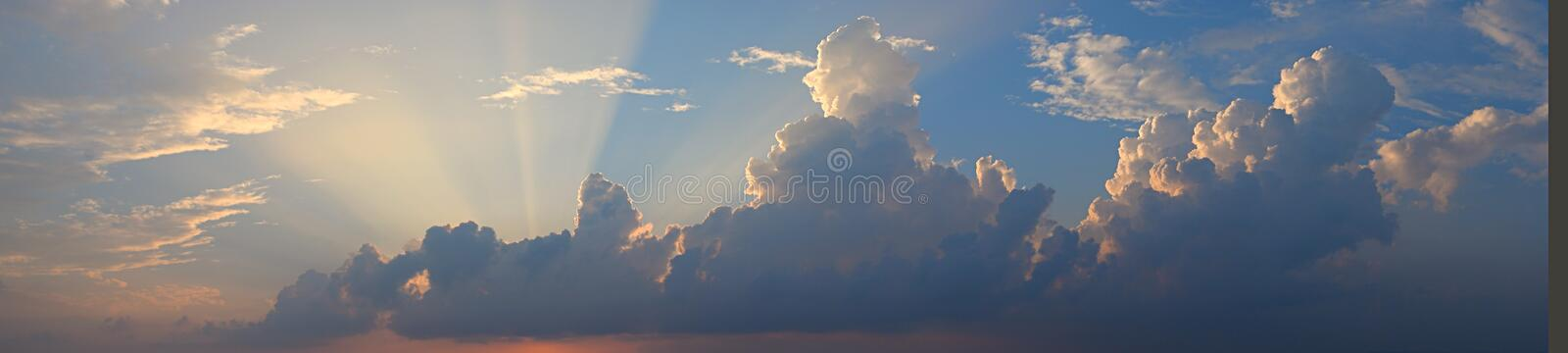 Golden Yellow Crepuscular Sun Rays from Dark Clouds in Blue Sky - Natural Background Skyscape stock images