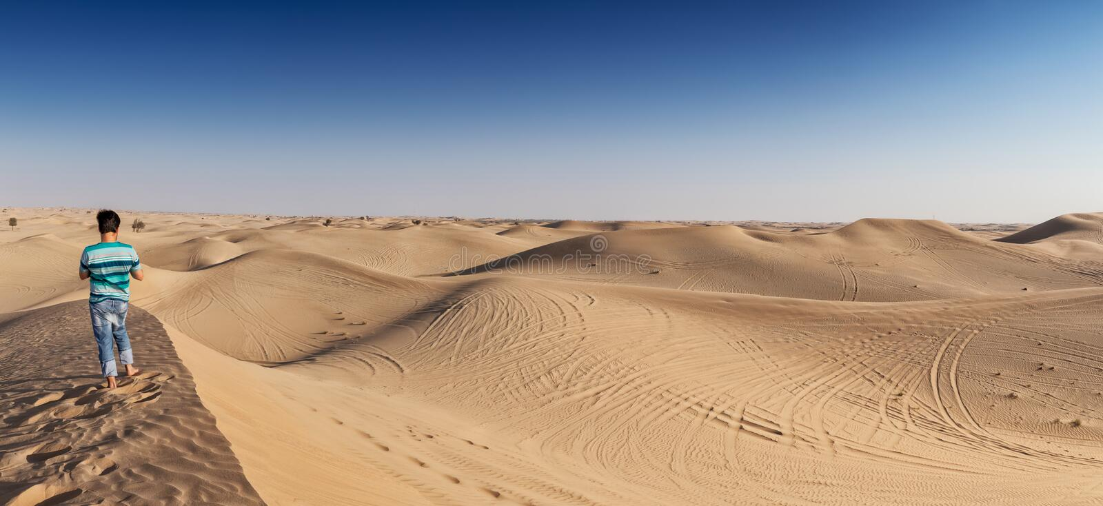 Panoramic photograph of a man on top of a dune in the Abu Dhabi desert. UAE. Uae stock image