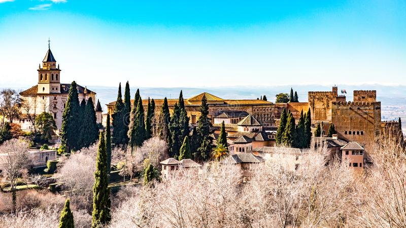 Panoramic picture of a ancient building in Andalusia Spain. Panoramic picture of a ancient building with leafless trees in the front and a blue sky on a stock photos
