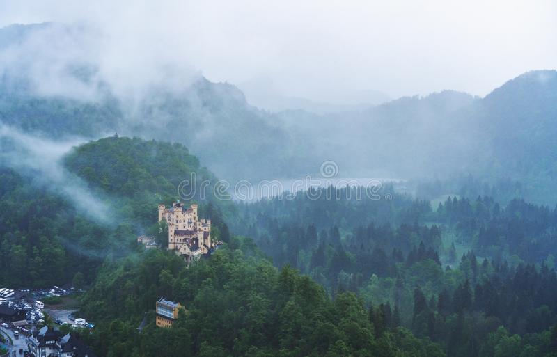 Panoramic pine forest and Hohenschwangau castle with foggy environment in Germany stock photography