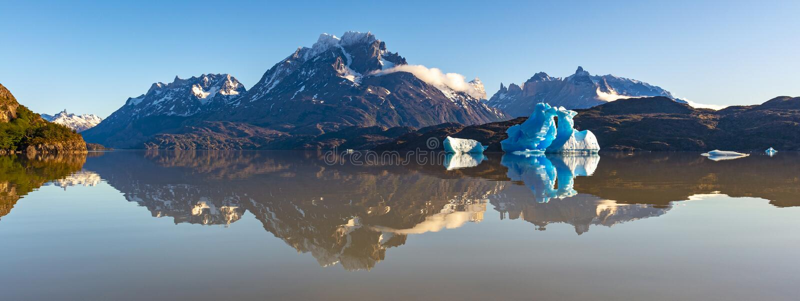 Panoramic Grey Lake, Patagonia, Chile. Panoramic reflection photograph of the Paine Grande and Cuernos del Paine Andes peaks in Lago Grey with blue iceberg at royalty free stock photography
