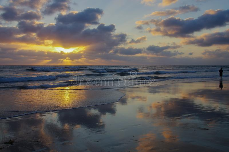 Panoramic scene of ocean sunset with clouds reflected on wet beach and person wading royalty free stock images