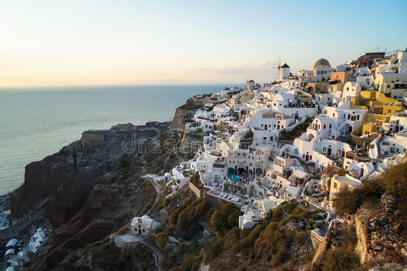 Panoramic scene in sunset light of Oia windmill and white building townscape along island natural mountain facing vast ocean royalty free stock photo