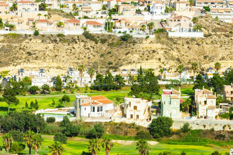 Panoramic scenic view of luxury golf and country club playing fields lawns surrounded by villas in Mediterranean style in Rojales royalty free stock photo