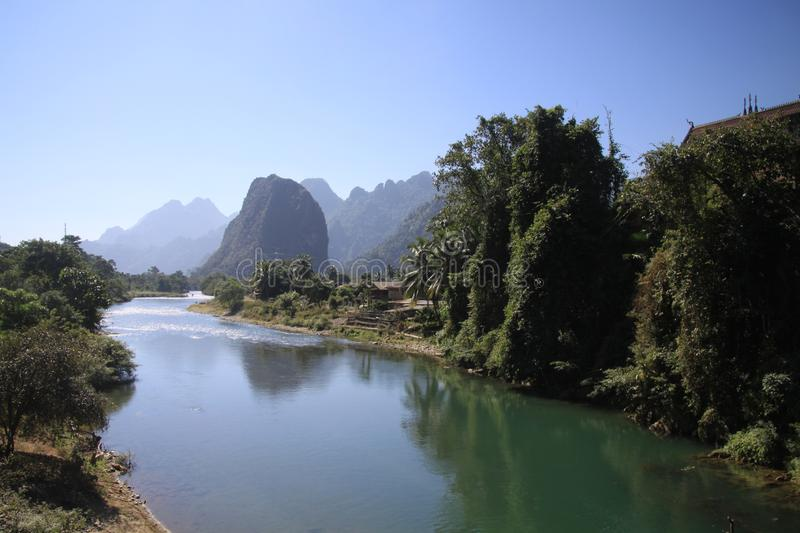 Panoramic scenic view of Nam Song Xong river amidst trees and rural karst hills landscape against blue clear sky , near Vang royalty free stock image