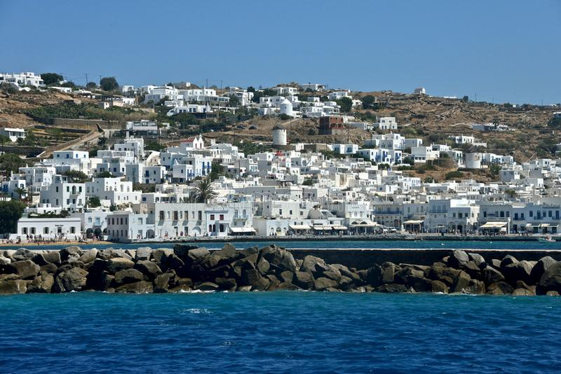 Seaside view of Mykonos with white buildings and pier made of rocks royalty free stock image