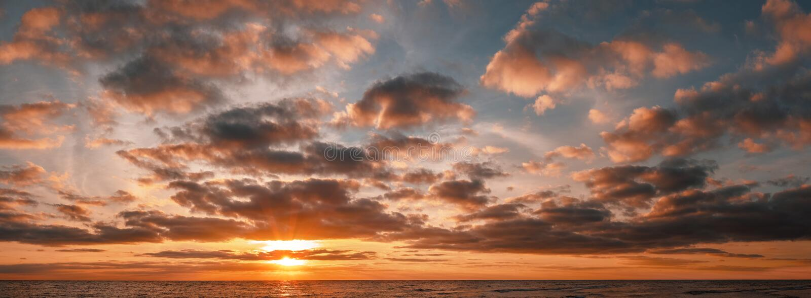 Panoramic shot of a sunrise over the ocean stock photos