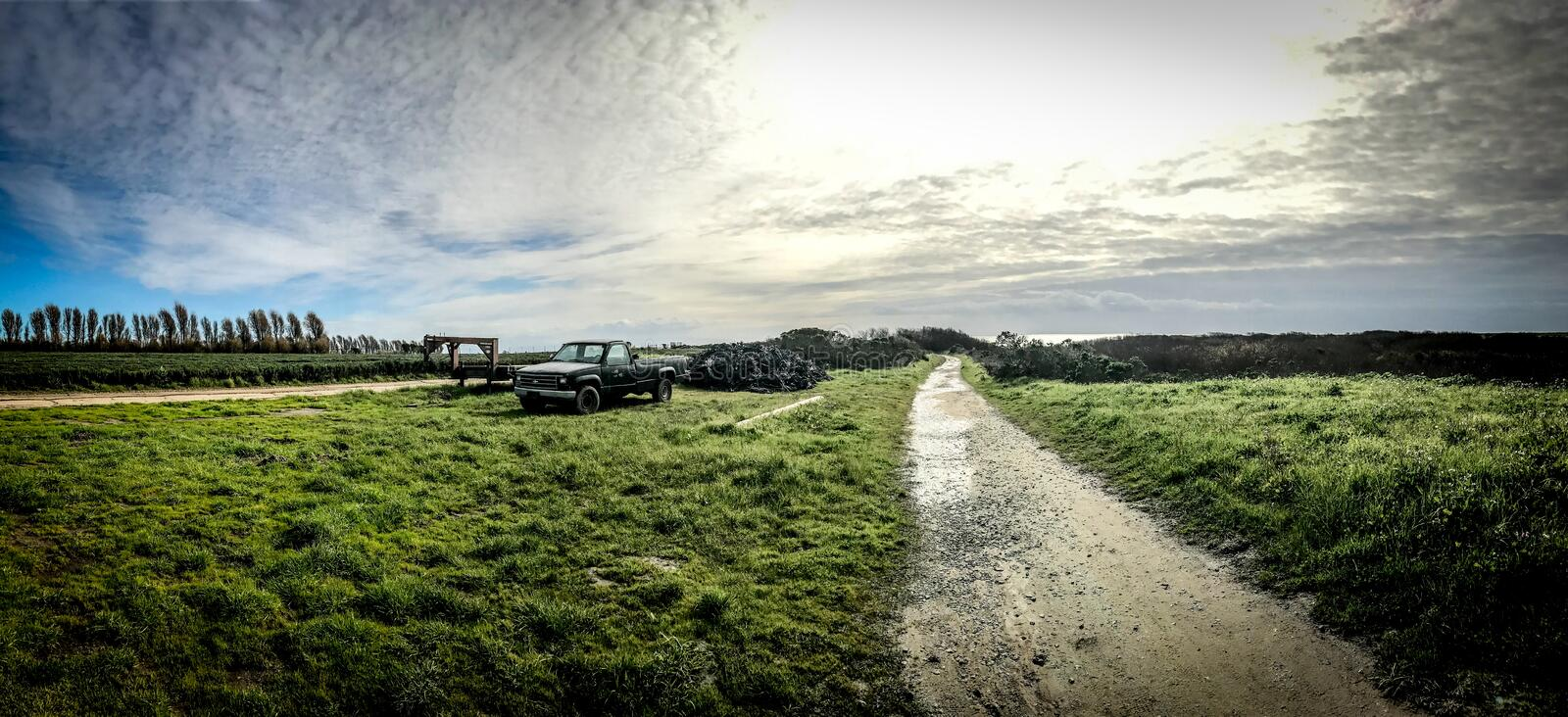 Panoramic shot of a green field with a narrow road in the middle and pickup truck parked on the side royalty free stock image