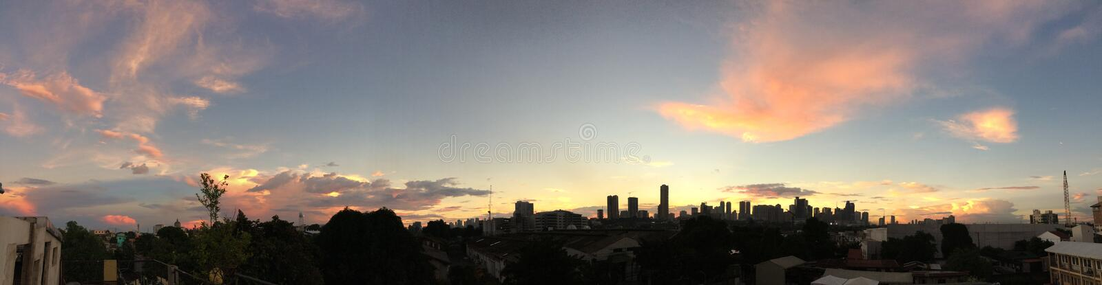 Panoramic shot of manila city buildings under a light blue sky at sunset. A panoramic shot of manila city buildings under a light blue sky at sunset royalty free stock photography