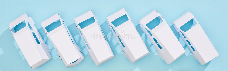Panoramic shot of miniature white autos on blue background. Panoramic shot of miniature white autos on blue background,stock photo stock photos