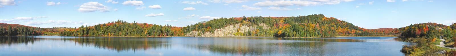 Large Panoramic of Northern Lake in Autumn. Panoramic shot of a Northern lake with calm waters on a blue summer day.  Hints of fall seasons colours showing stock image