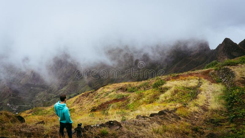 Panoramic shot of traveler taking picture of amazing steep mountain range and terrain canyon valley on the path from Xo. Xo Valley. Camera on tripod.Santo Antao royalty free stock photos