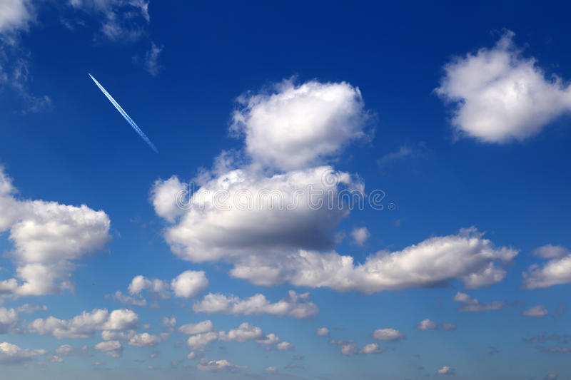 Panoramic sky. Panoramic view of blue sky, bright cloudy day and aircraft smoke stock image